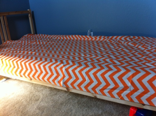 Please feel free to measure your bed... I, however, choose something more exact.  I just place my fabric over the bed.  Turns out this fabric is exactly the right width.  Whew.  Let's assume for the sake of this tutorial that yours is too.  (If it's not wide enough, that requires an additional step or two - for another day)