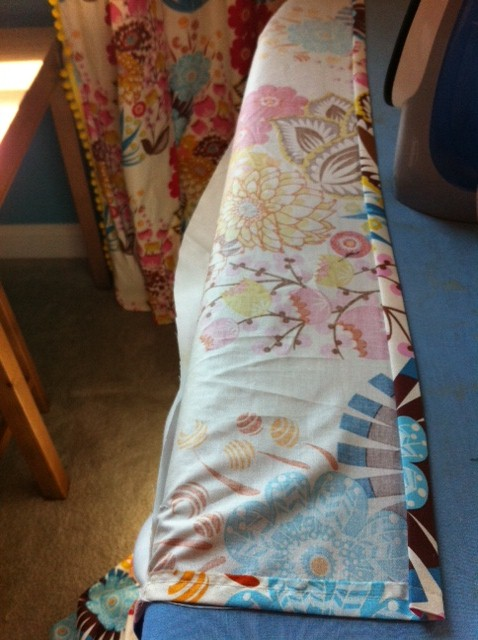 Almost done y'all!  Put the bottom of the curtain on your ironing board and press a small seam...about 2 inches.  Sew that hem up!