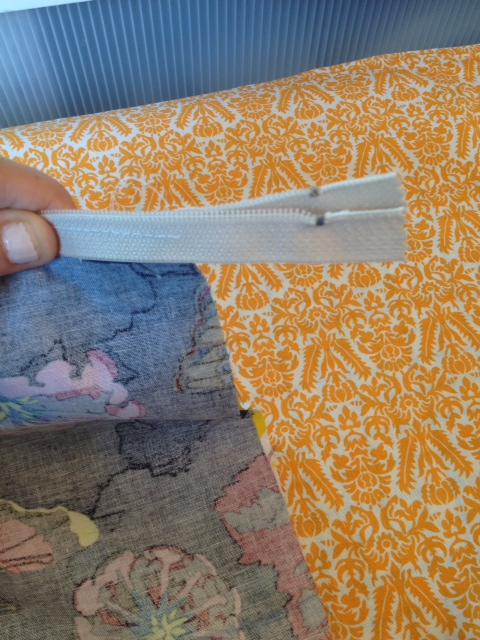 Now fold the two sections over, right sides together and fold the open zipper parts like this.  Next, you'll sew down along the side, the bottom and back up the other side - forming a stitched square (the zipper making the 4th side).